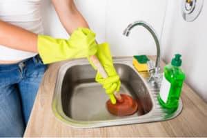 Photo d'une personne en train de déboucher un évier avec une ventouse