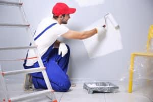 Un peintre en bâtiment, en train de peindre un mur en blanc.