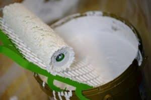 Photo d'un sceau de peinture blanche avec le rouleau de peinture en train, de s'essorer